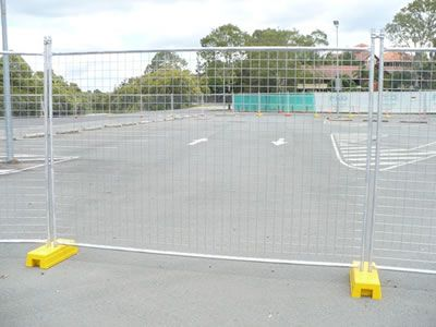 Australian temporary fencing is installed in a parking lot.