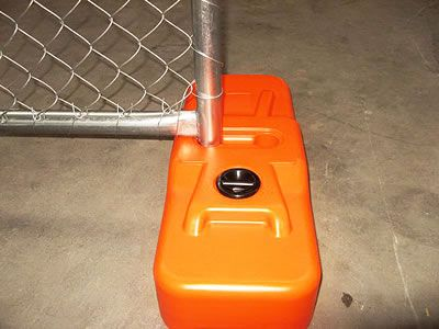 There is a piece of chain link portable fence with plastic feet.