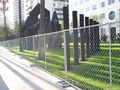Temporary chain link fences are set on the sidewalk.