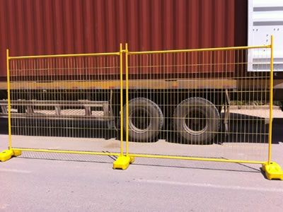 Two pieces of yellow Australian temporary fences are standing in front of a truck.