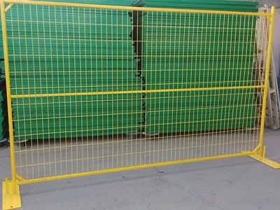 yellow canada temporary fence is being set in front of green ones